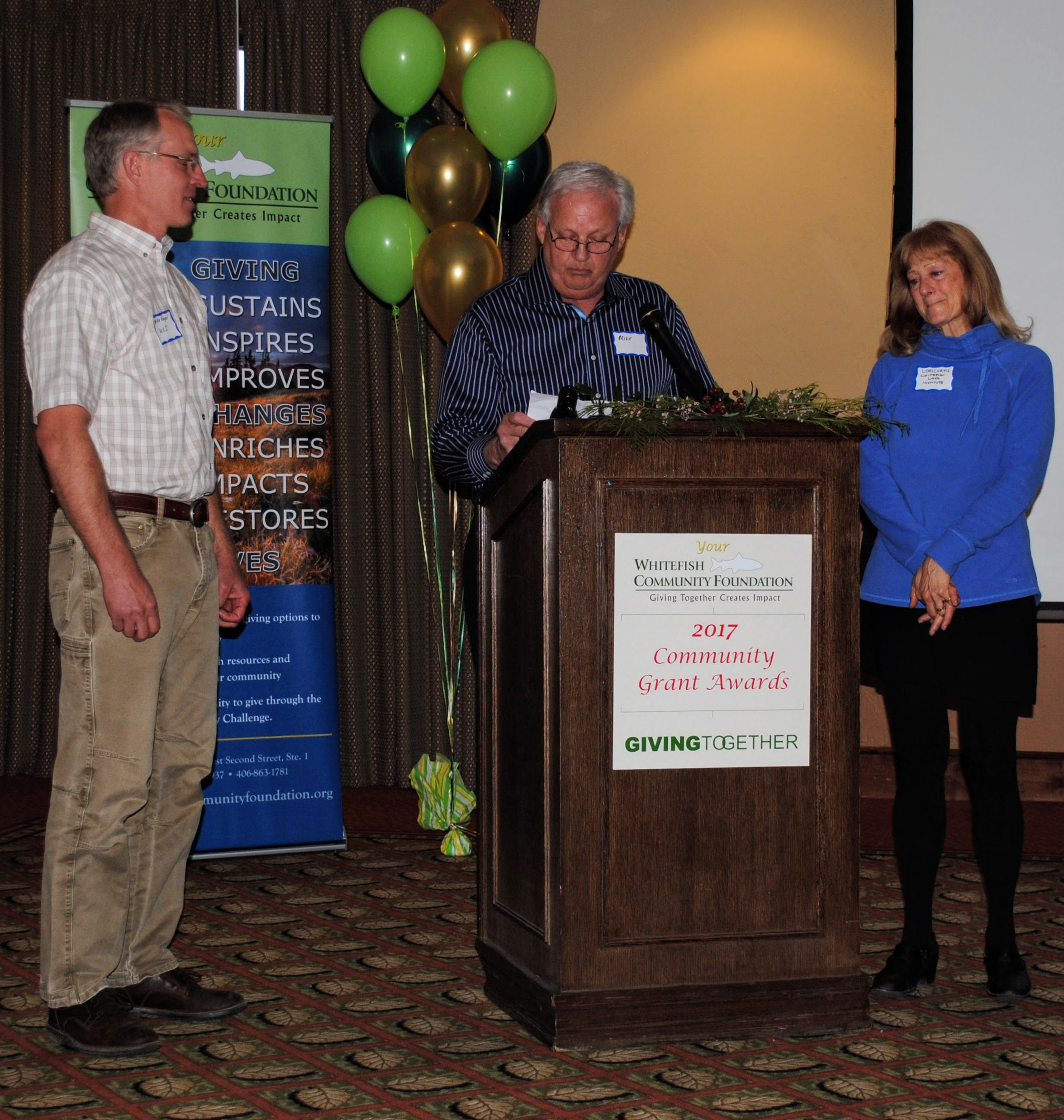Board Member Mike Jenson presents the Mary Jane and Russ Street Community Service Award to Mike Koopal and Lori Curtis, with Whitefish Lake Institute.
